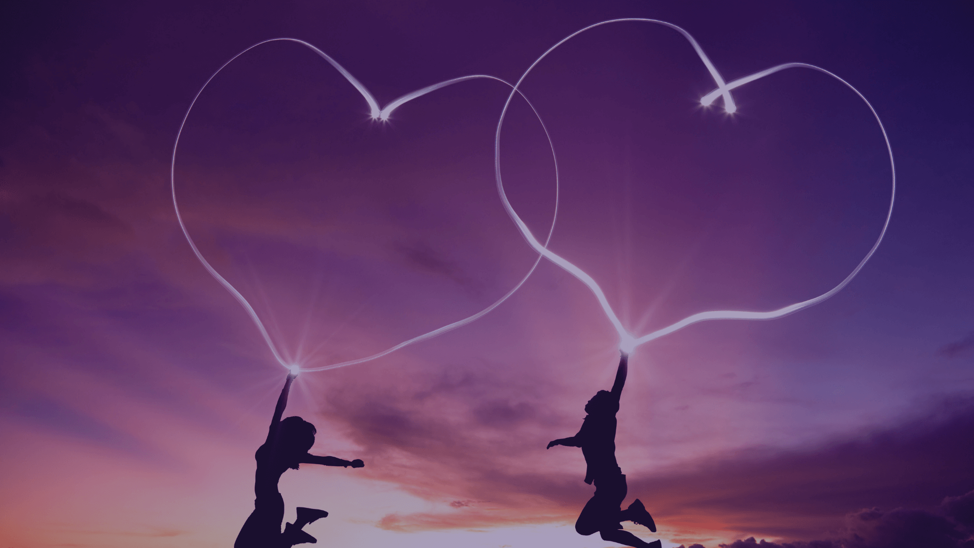 two people jumping in celebration against sunset