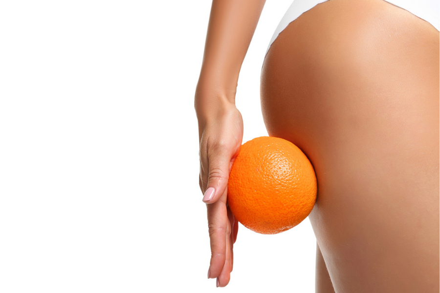 Woman rolling orange on her thigh